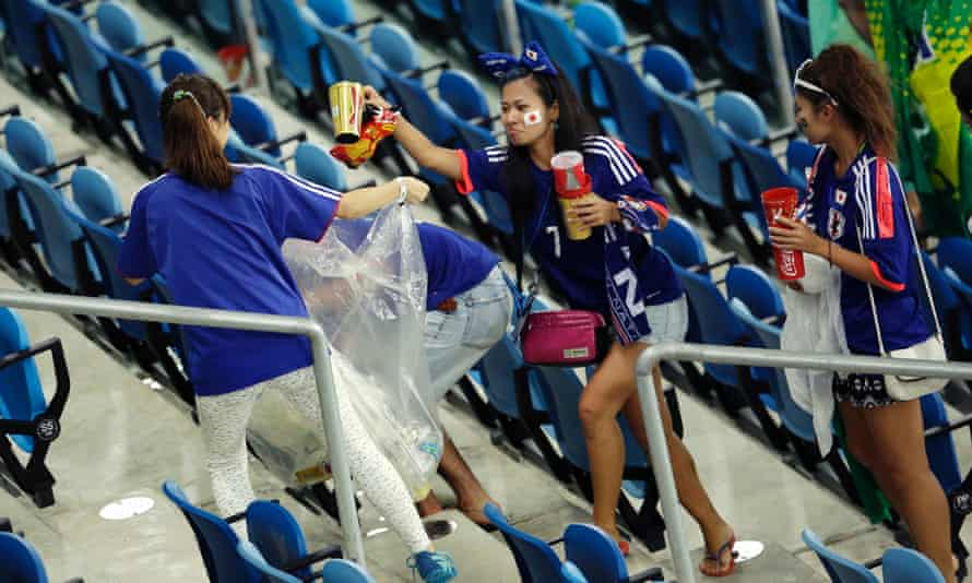 Japan fans collect rubbish after their game against Greece.