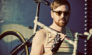 A fixed gear rider in a yellow striped tank top and sunglasses poses
