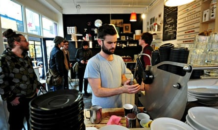A man makes coffee at a cafe in Brixton.