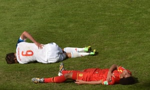 Two footballers, lying on the floor ... possibly snoozing ... due to all the boring football.