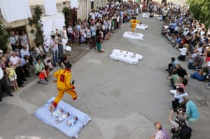 A man dressed up as the devil jumps over babies lying on a mattress in the street during El Colacho. Photograph: Cesar Manso / AFP / Getty Images