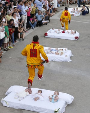 A man dressed up as the devil jumps over babies lying on a mattress in the street during El Colacho, the baby jumping festival in the village of Castrillo de Murcia. Photograph: Cesar Manso / AFP / Getty Images