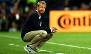 USA head coach Jurgen Klinsmann crouches on the sidelines.