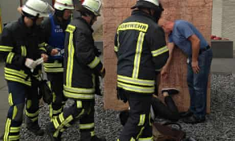 Firefighters consider how to free the student from the vagina sculpture