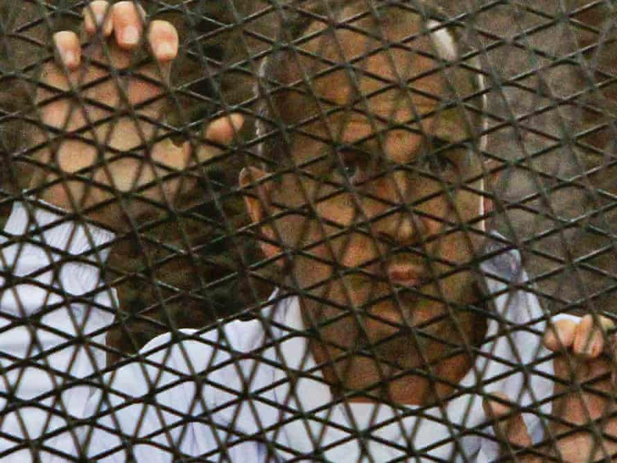 Peter Greste stands inside the defendants' cage in the Cairo courtroom.