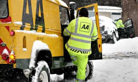 AA rescue service help a motorist whose car is stuck in the snow.