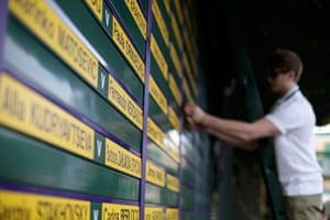 wimbo day 1: A worker adds names to the results board