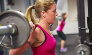 Woman in pink sports top lifts barbells in gym