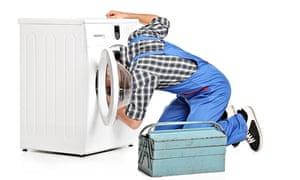 A repairman trying to fix a washing machine