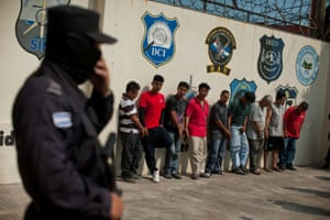 Alleged gang members and collaborators stand after a raid in San Salvador, El Salvador