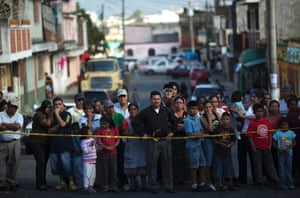 Bystanders stand behind police tape at a crime scene in Guatemala City