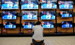 A man crouches in front of TV sets showing the England Uruguay match