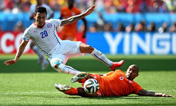Charles Aranguiz of Chile is tackled by Nigel de Jong of the Netherlands