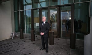 """Independent MP Andrew Wilkie waits his turn to speak to the media at the ritual known as """"reps doors"""" at Parliament House Canberra."""