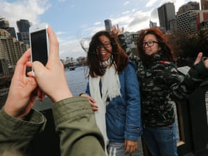 Tourists try to take a photo in the wild weather in Melbourne on Tuesday