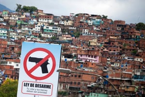 A billboard promoting a ban on guns in front of Petare, the largest slum in Caraca