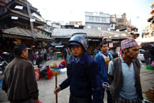 A temporary police officerl, recruited for the constituent assembly elections, patrols around the market in Kathmandu