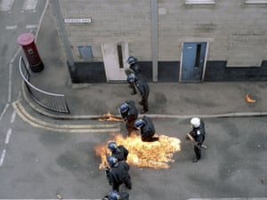 A petrol bomb explodes at the feet of a line of officers during an exercise.