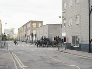 Officers on horses ride through the streets.