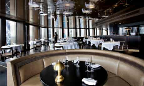 Curved banquette with round tables behind it at City Social