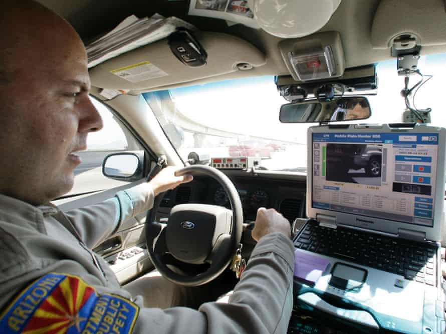 Arizona Department of Public Safety officer David Callister keeps an eye on his dashboard computer as it reads passing car licence plates.