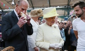 Prince Phillip gets into the local produce whilst the Queen chats with stall holder Simon Matthews