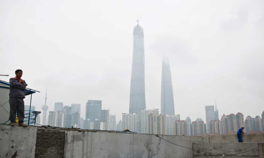 Construction workers stand on a wall at a construction site near Pudong financial district in Shanghai. Outward investment in China is set to be higher than investment into the country within three years.