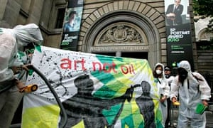 Campaigners dressed as a mock clean-up crew called the 'Greenwash Guerrillas' hold a banner outside