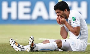 Luis Suárez holds his teeth after appearing to bite Italy's Giorgio Chiellini.
