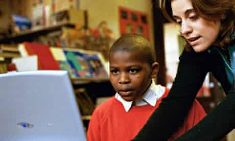 A teacher helps a boy in red school sweater working at a laptop