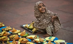 A Muslim girl arranges plates before iftar (breaking fast) meal on the first day of the holy month of Ramadan in India at the Jama Masjid (Grand Mosque) in the old quarters of Delhi