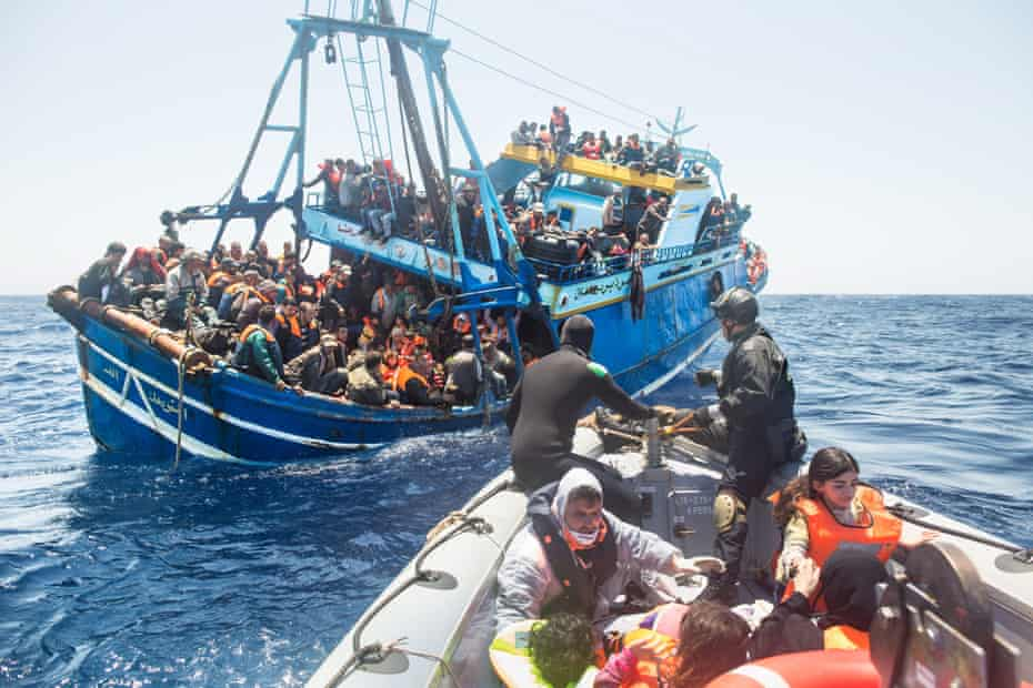 Refugees on board a fishing vessel carrying 443 Syrian asylum seekers are rescued by the Italian navy