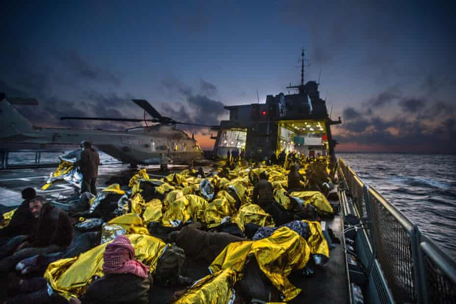 Syrian refugees on an Italian navy ship after being rescued from a fishing vessel carrying 443 Syrian asylum seekers, 5 June.