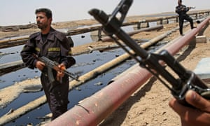 Iraqi police officers protecting oil installations secure an oil pipeline from the Rumailah refinery, north of Basra, in 2008.