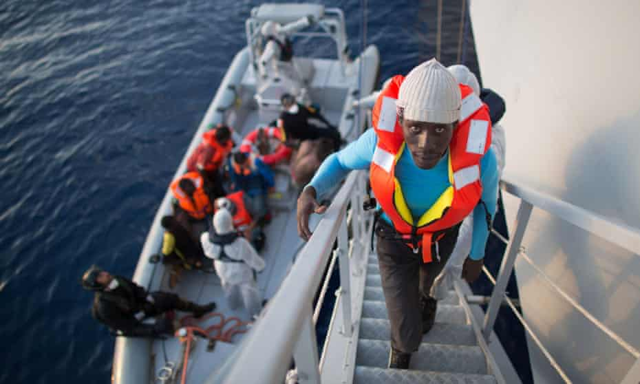 African asylum seekers rescued off boats and taken aboard an Italy navy ship.