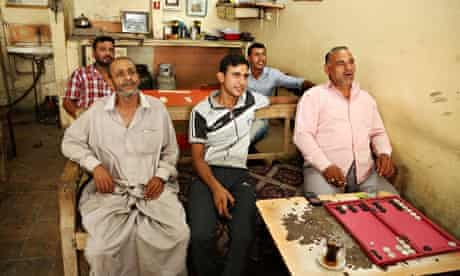 group of five men watch the iraqi prime minister on television in a baghdad cafe