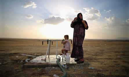A women and a girl wash at a tap at a temporary displacement camp set up next to a Kurdish checkpoint on June 13, 2014 in Kalak, Iraq. Thousands of people have fled Iraq's second city of Mosul after it was overrun by ISIS (Islamic State of Iraq and Syria) militants.