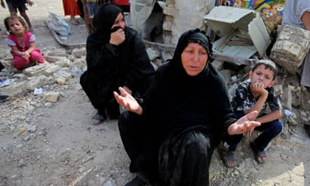 Iraqi women at a collapsed building the day after a bombing in Baghdad, Iraq, in 2010.