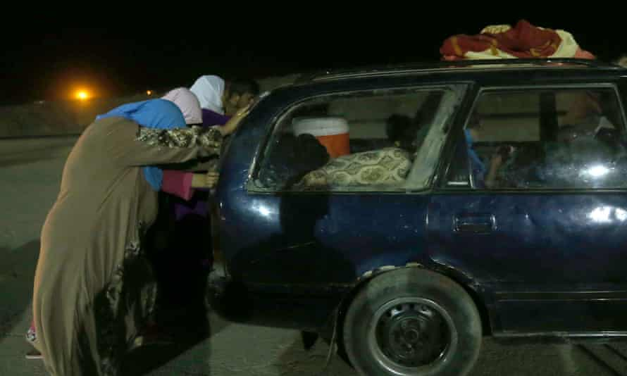 Iraqi women, fleeing from a northern Iraqi town, help push a car after it broke down, between the Mosul and the Kurdish city of Irbil, in northern Iraq, on Wednesday.