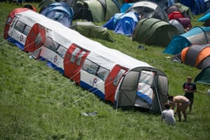 People pitch a London Underground train tent in the camping fields