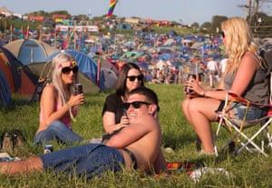 Festival goers relax in the sunshine.