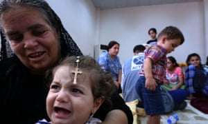 An Iraqi Christian woman fleeing the violence in the village of Qaraqush, about 30 kms east of the northern province of Nineveh, plays with a child upon her arrival at a community center in the Kurdish city of Irbil in Iraq's autonomous Kurdistan region.