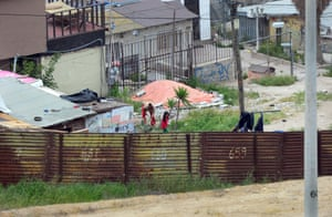 Residents of Tijuana, Mexico,seen from across the fence.