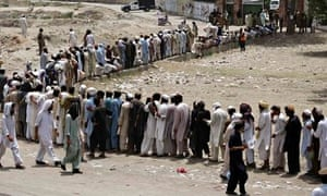 People line up to receive food supplies in Bannu, Pakistan