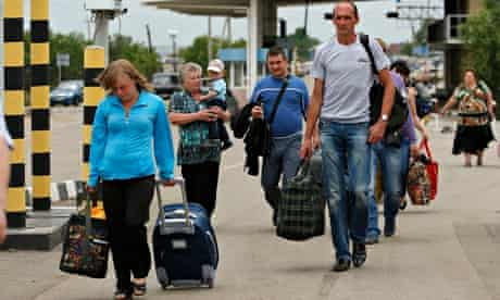 Ukrainians enter Russia at a border checkpoint in the Luhansk region, as thousands flee the fighting