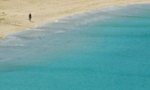 A tourist walks along the tsunami-damaged Kamala beach in Thailand's Phuket