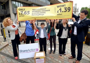 A small group of people from protest group ShareAction demonstrate outside the QEII conference centre, against the below living wage paid to some workers at supermarket giant Tesco.