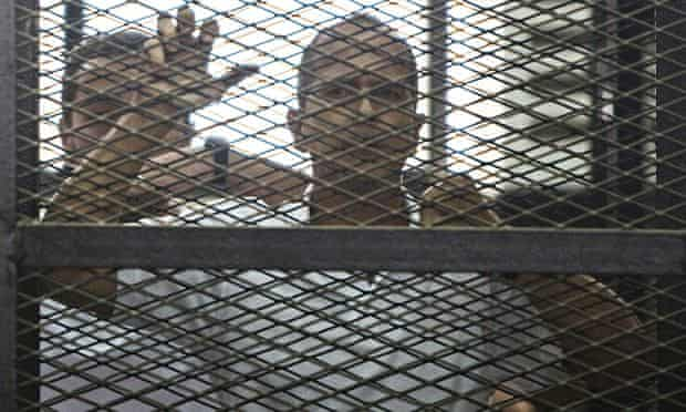 Peter Greste stands inside a cage in an Egyptian courtroom