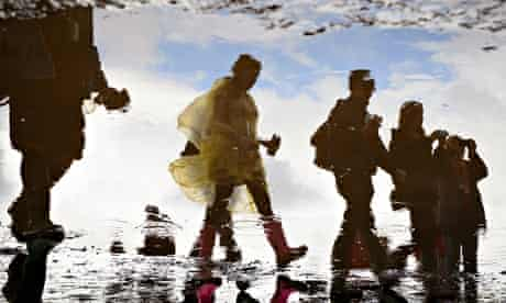 People are reflected in a puddle on the first official day of the Glastonbury festival