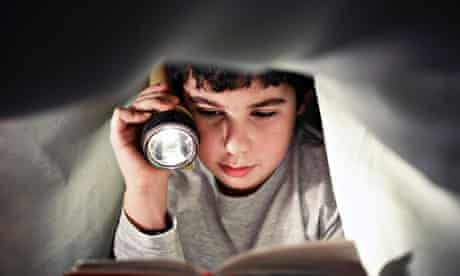 boy reading book under the covers. Copy space